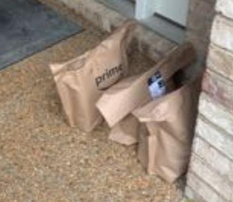 Amazon Fresh bags next to door.