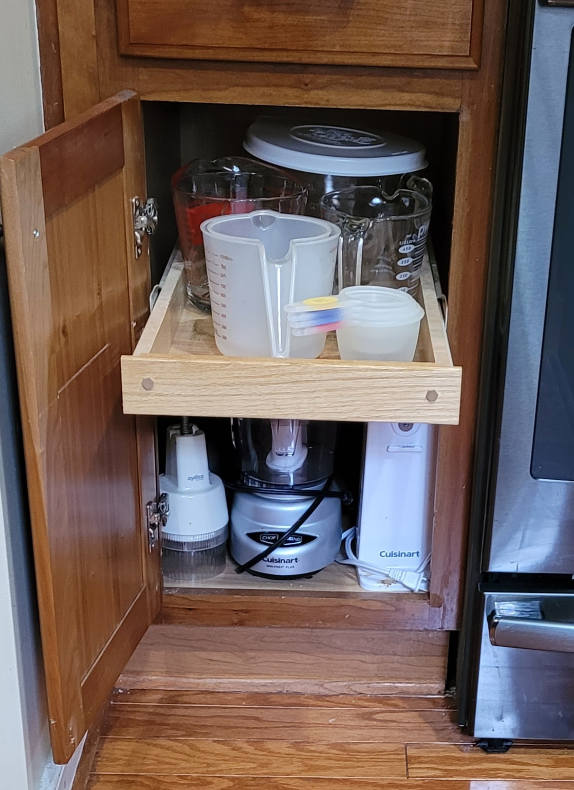Cabinet pull out shelf with measuring cups.