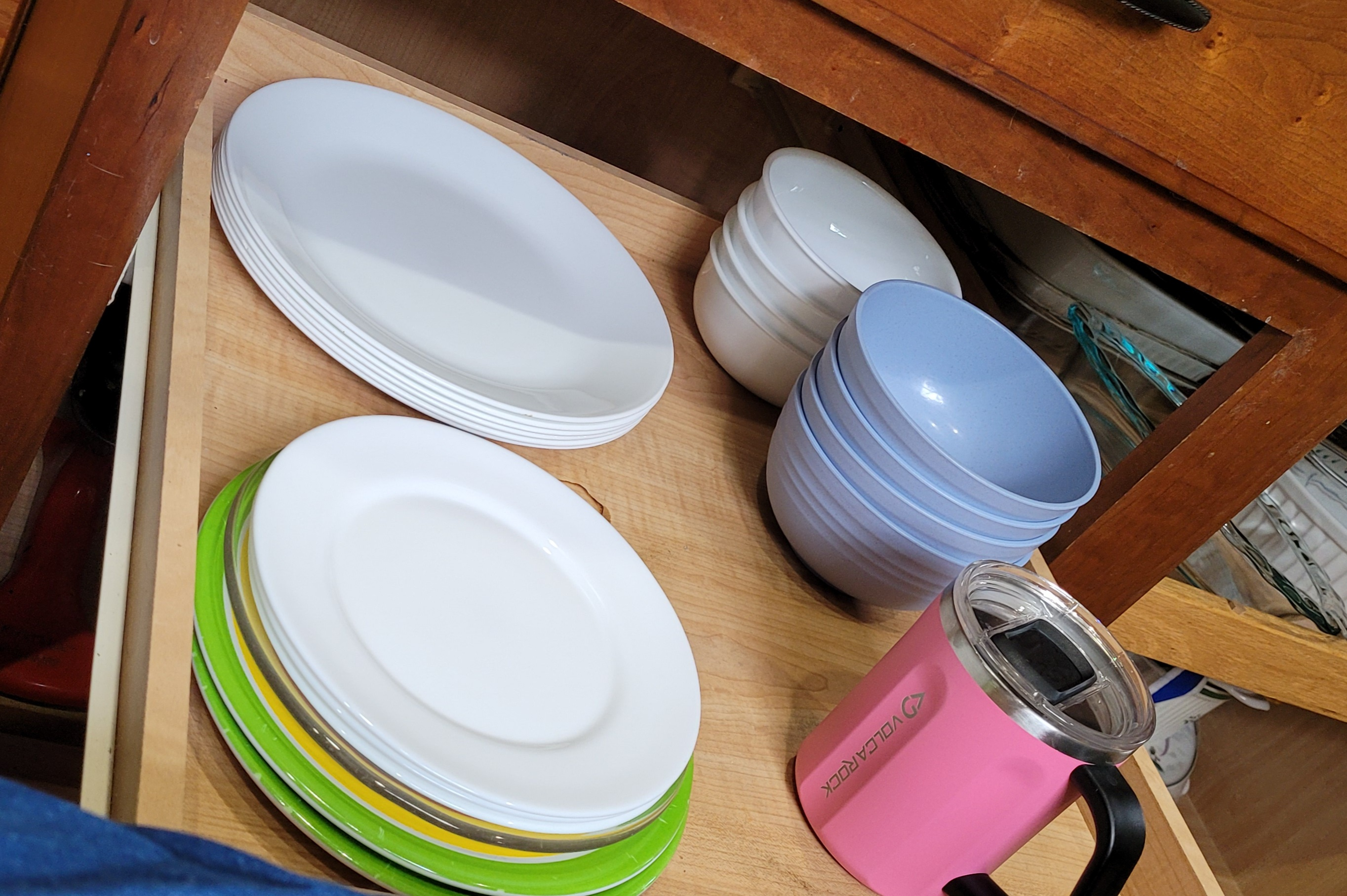 Cabinet pull out shelf with plates, bowls, and travel mug.